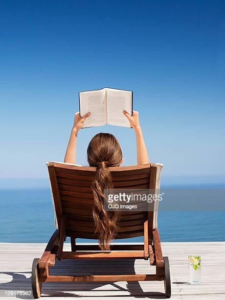 Femme lisant un livre sur une chaise de la terrasse