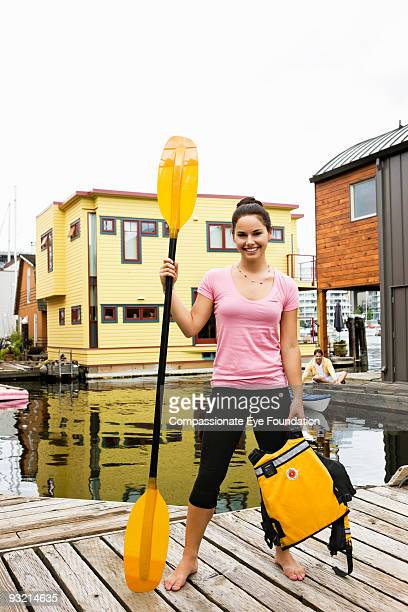 """woman on dock holding paddle and life jacket - """"compassionate eye"""" fotografías e imágenes de stock"""