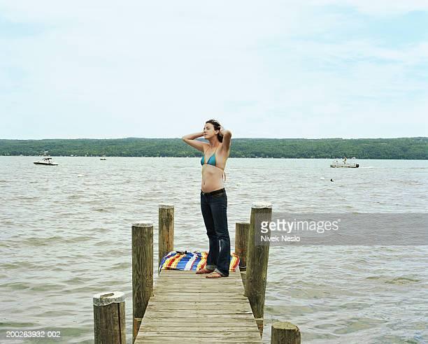 Woman on dock on lake fixing hair