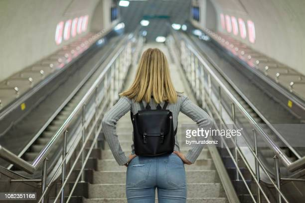 woman on escalator in subway station - moving activity stock pictures, royalty-free photos & images