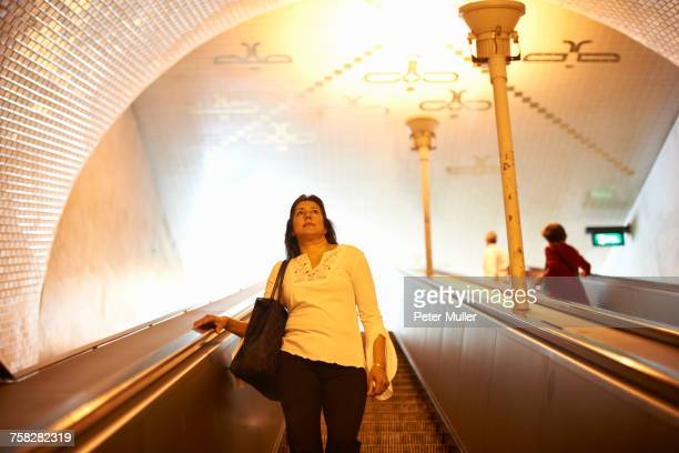 woman on escalator, lisbon, portugal - down blouse stock photos and pictures