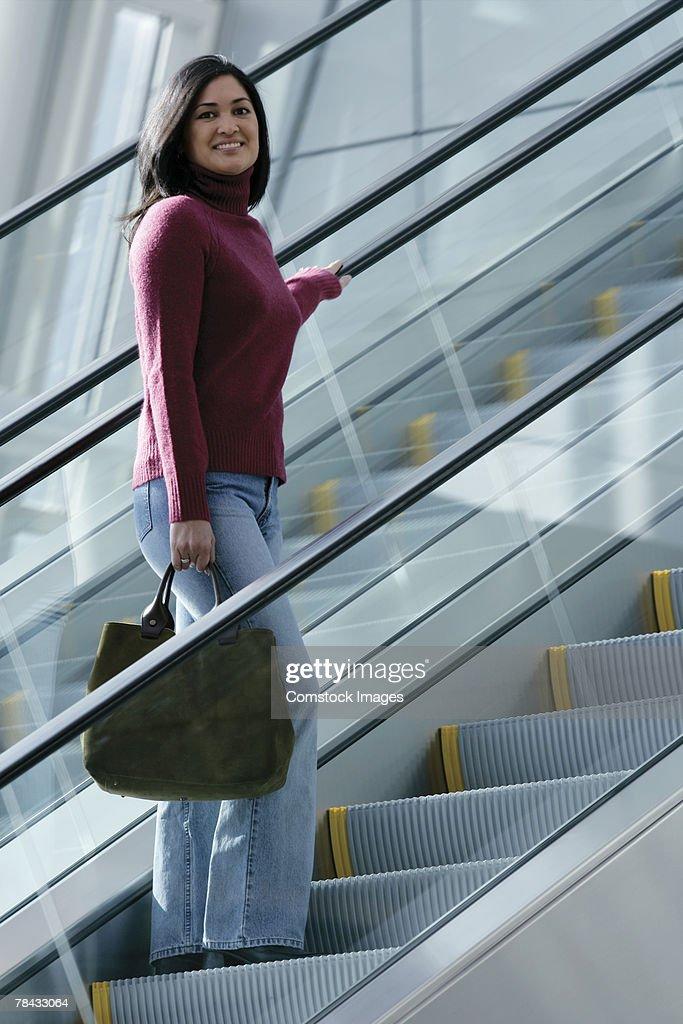 Woman on escalator : Stockfoto