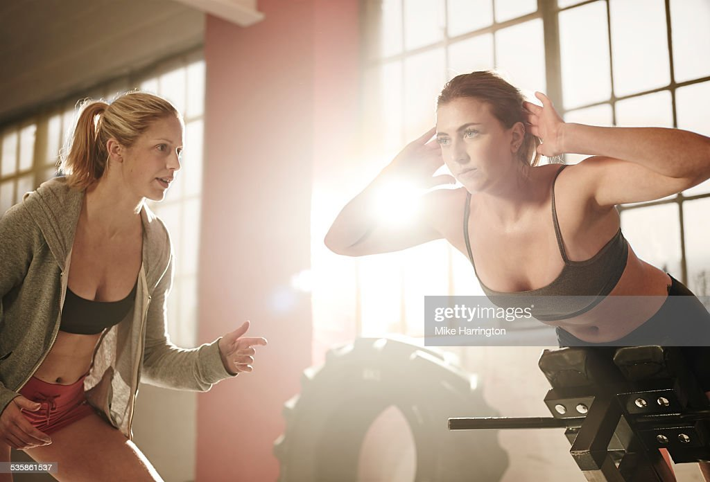 Woman on extension bench in industrial gym : Stock Photo