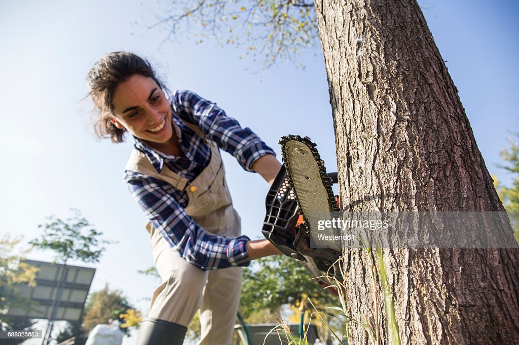 Woman on farm cuttiing tree with chain saw : Stock Photo