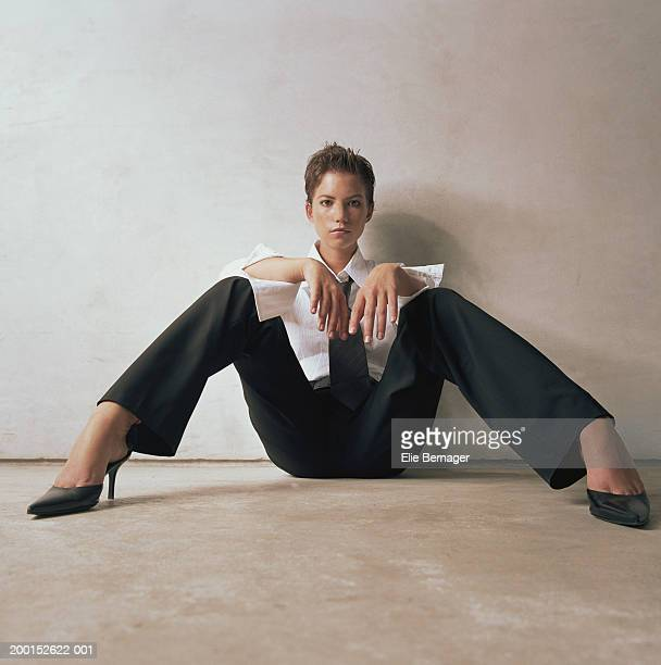 Woman on floor leaning against wall, resting arms on knees, portrait