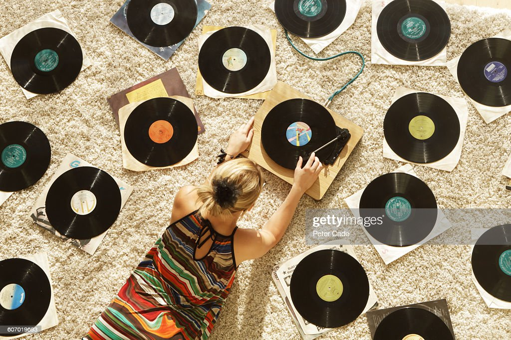 Woman on floor playing records : Stock Photo