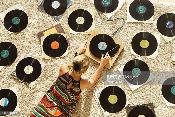 woman on floor playing records - vinylplaat stockfoto's en -beelden