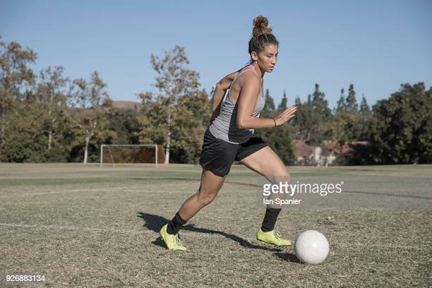 woman on football pitch playing football - dribbling stock pictures, royalty-free photos & images