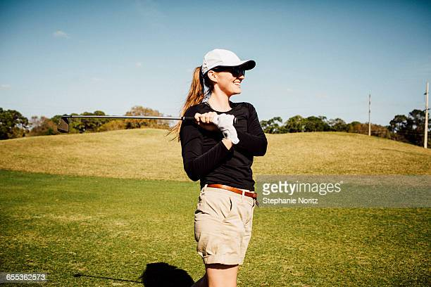 Woman on golf course watching her shot