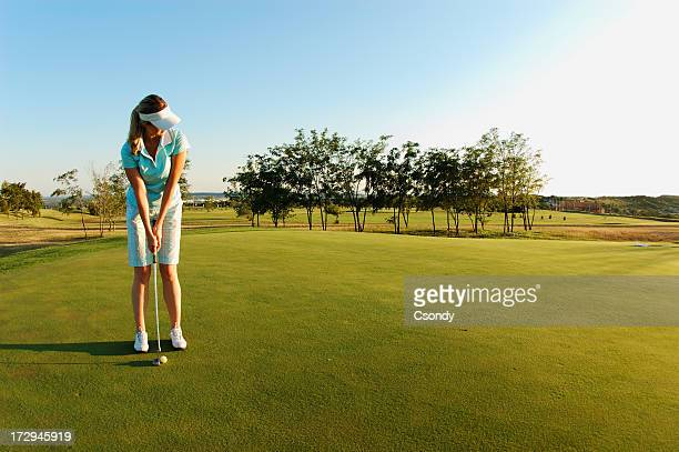 Woman on golf field ready to put ball