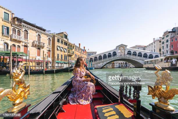 woman on gondola and rialto bridge, venice. - gondola traditional boat stock pictures, royalty-free photos & images