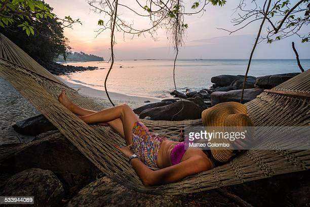 woman on hammock enjoying sunrise on a beach - phi phi islands stock-fotos und bilder