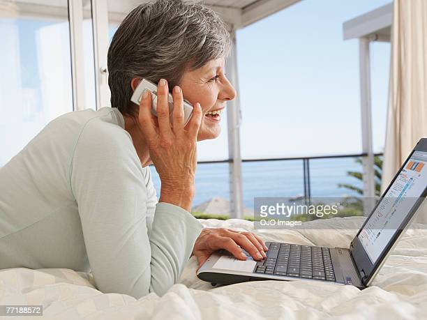 A woman on her cellular phone using a laptop