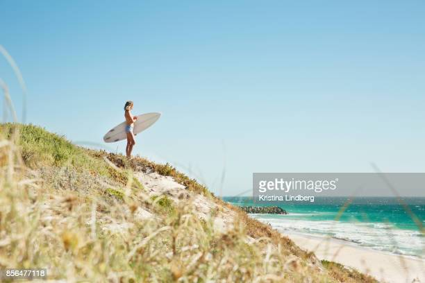 Woman on hill with surfboard looking to the sea