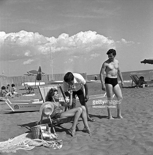 A woman on holiday being courted by two men at the beach while her husband is still working in town One of them lights his cigarette straight from...