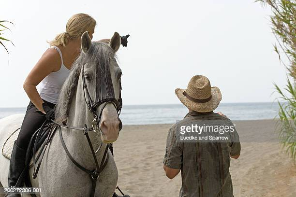 Woman on horse by man, pointing out to sea, rear view of man