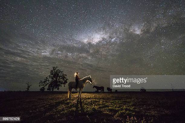 woman on horse under the stars in australia. - andare a cavallo foto e immagini stock