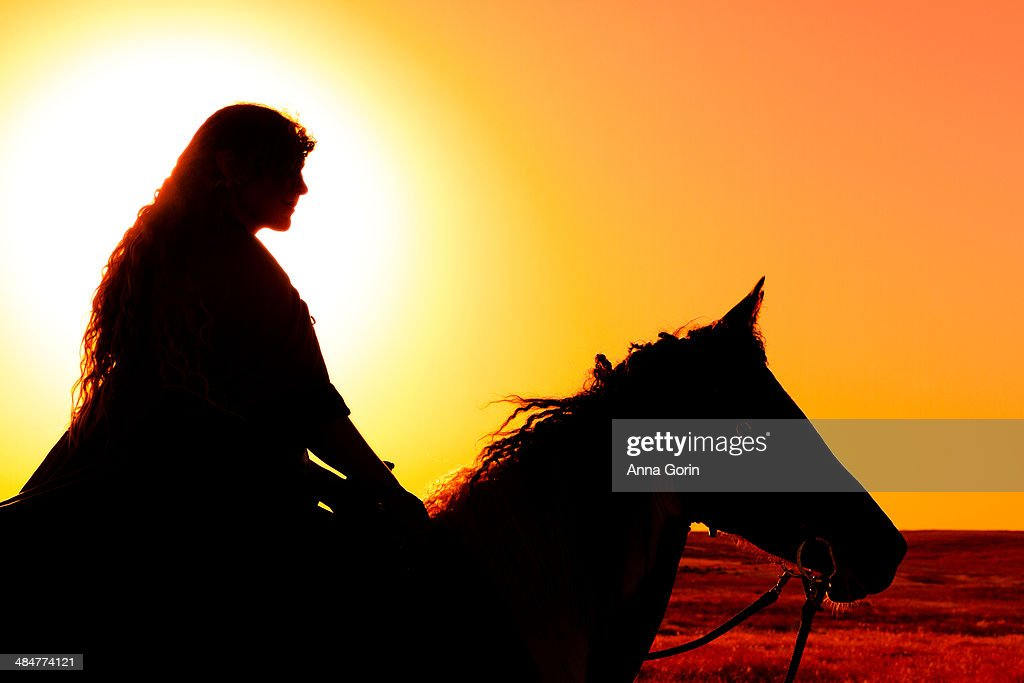 Woman on horseback silhouetted against setting sun : Stock Photo