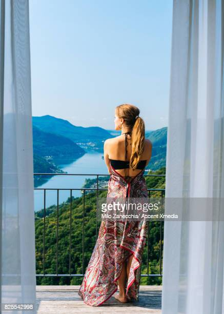 woman on hotel balcony overlooks view of lake and mountains - garde corps photos et images de collection