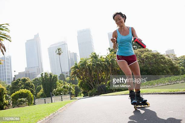 Woman on inline skates looking at mp3 player