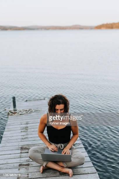 woman on jetty using laptop - leisure activity stock pictures, royalty-free photos & images