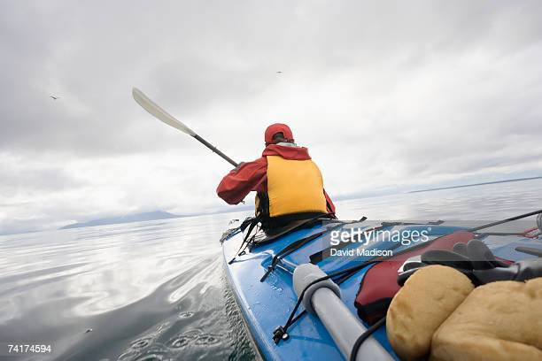 """""""woman on kayak in sea, rear view"""" - sea kayaking stock pictures, royalty-free photos & images"""
