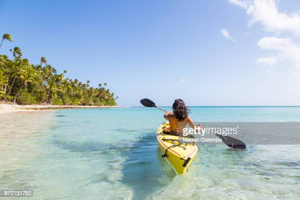 woman on kayak near beach in a tropical island, fiji - kajak stock-fotos und bilder