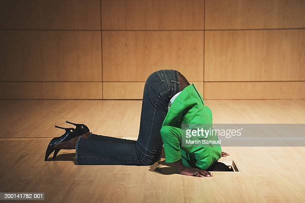 Woman on knees looking through hole in floor