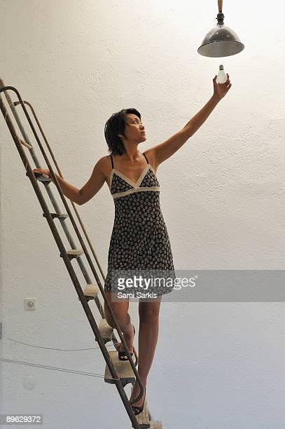 Woman on ladder changing light bulb