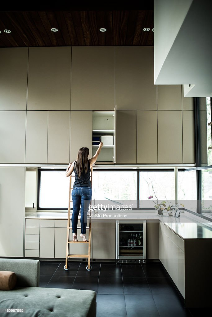woman on ladder looking in cabinet : Stock Photo