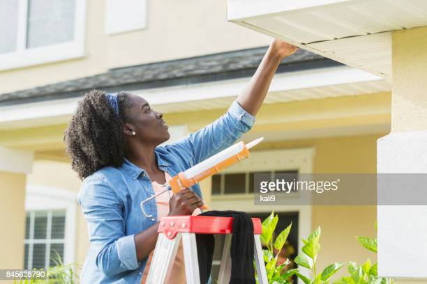 woman on ladder outside house doing repairs - home improvement stock pictures, royalty-free photos & images