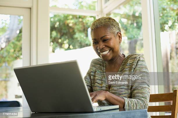 woman on laptop at a table smiling - 50 54 years stock pictures, royalty-free photos & images