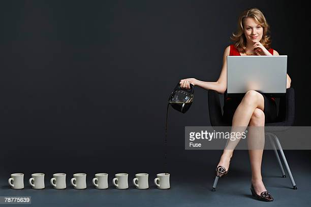 Woman on Laptop Pouring Coffee into Mugs