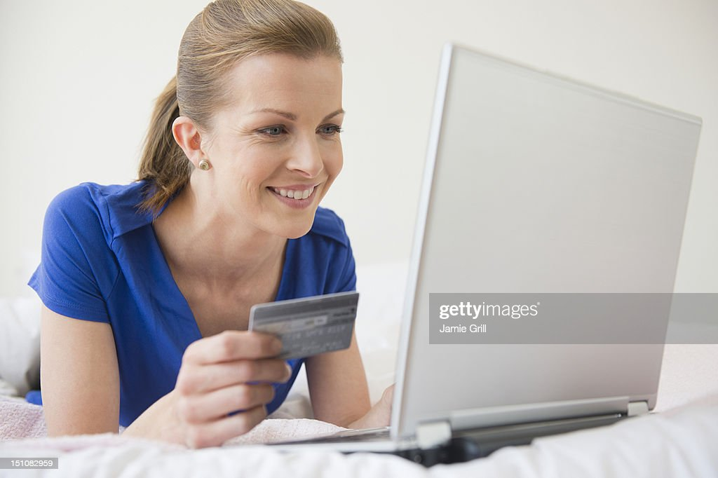 Woman on laptop with credit card : Stock Photo