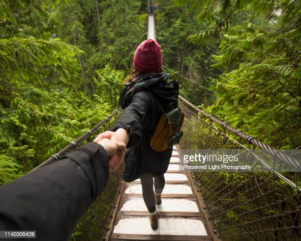 woman on lynn canyon suspension bridge holding mans hand, north vancouver, british columbia, canada - suspension bridge stock photos and pictures