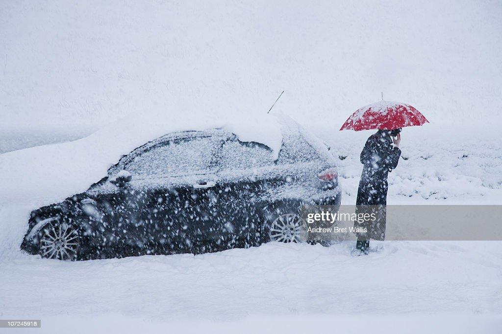 woman on mobile alongside car in a snow drift : Foto de stock