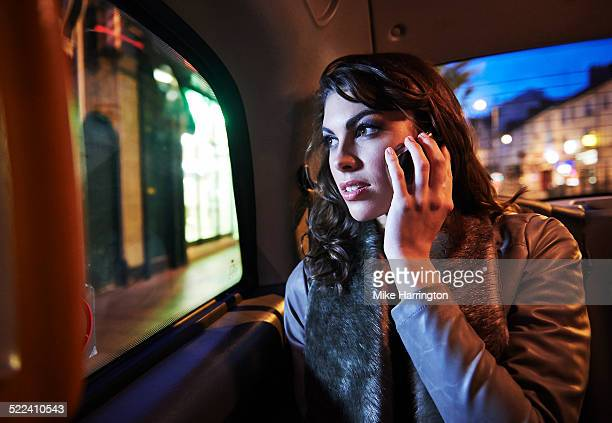 Woman on mobile phone looking out of taxi window