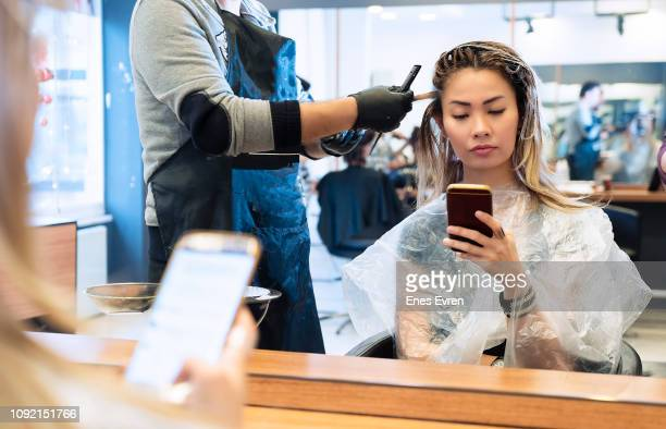 woman on mobile phone when having hair coloring process in a hair salon - colouring stock photos and pictures