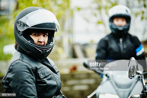 Woman on motorcycle preparing to ride with friends