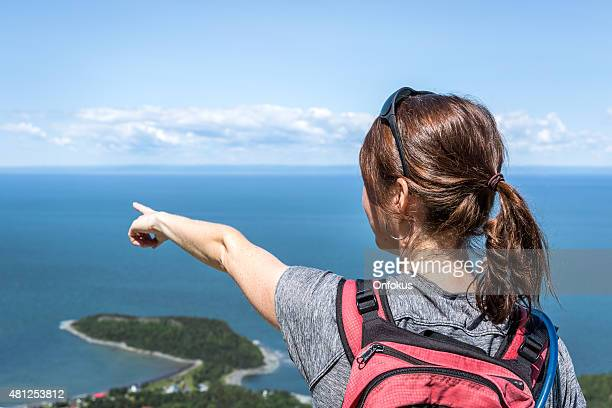 Woman on Mountain Summit Pointing a Direction