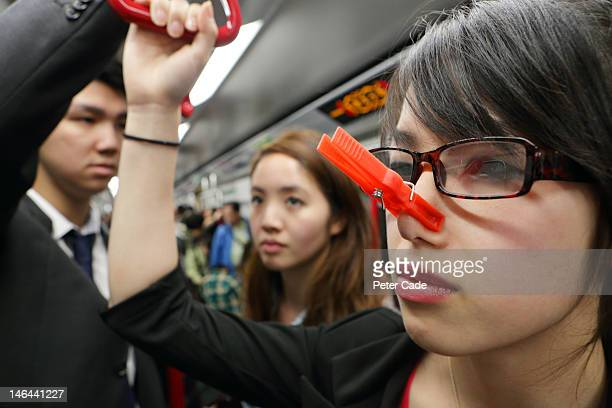 woman on MTR with peg on nose
