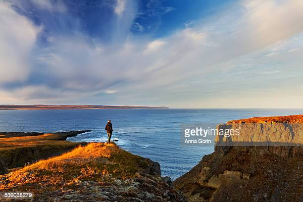 Woman on ocean cliffs in Vopnafjörður, Iceland