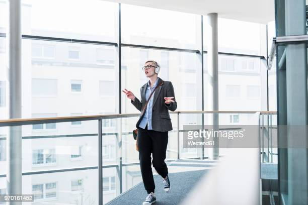 woman on office floor enjoying listening to music with headphones - music halls stock pictures, royalty-free photos & images