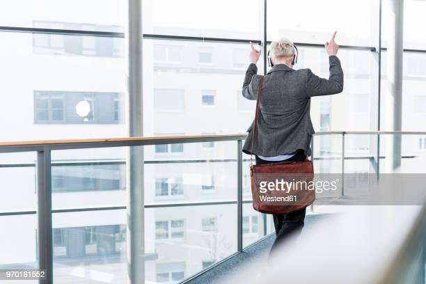 woman on office floor enjoying listening to music with headphones - crossbody bag bildbanksfoton och bilder