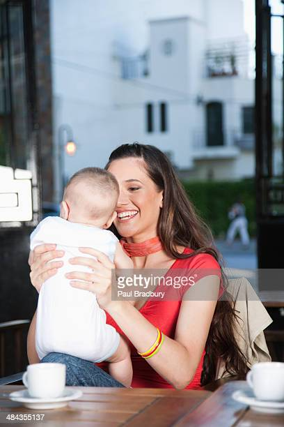 woman on outdoor patio holding baby and smiling - birthing chair stock pictures, royalty-free photos & images