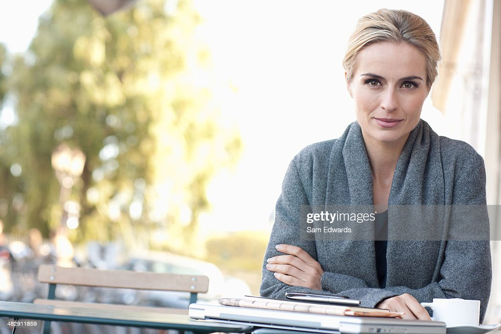Woman on outdoor patio with coffee : Stock Photo