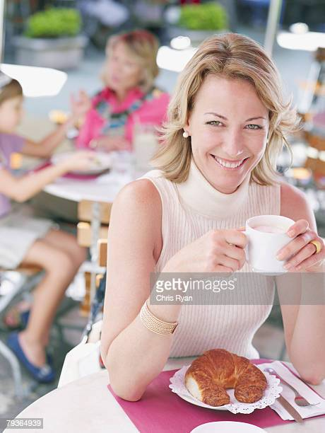 Woman on outdoor patio with croissant and coffee