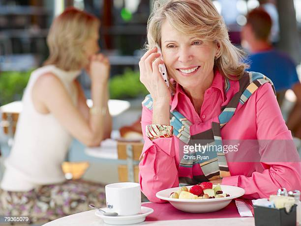 woman on outdoor patio with her mobile phone and fruit bowl - 40 49 years stock pictures, royalty-free photos & images