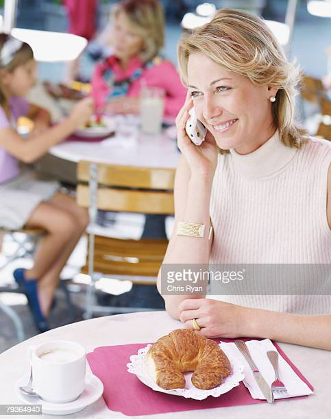 Woman on outdoor patio with mobile phone and croissant