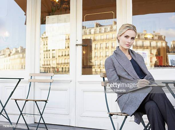 Woman on outdoor patio writing in notebook